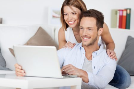 21162440 - cheerful couple searching something on laptop at home